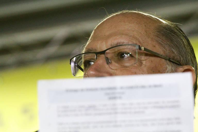 Geraldo Alckmin com folha de sulfite encobrindo metade do rosto durante discurso