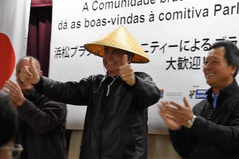 O deputado Jair Bolsonaro é recebido por apoiadores em Hamamatsu, no Japão.  Ele usa um chapéu de palha japonês em forma de cone.