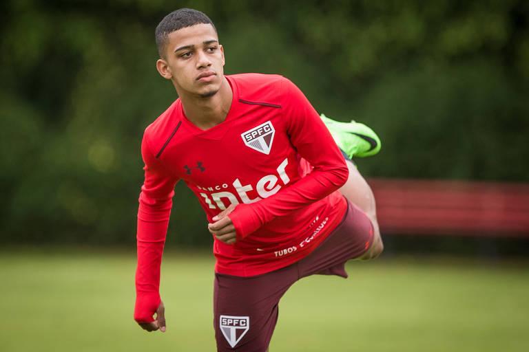 O jogador Brenner, com uniforme do São Paulo, faz exercícios físicos durante treinamento do time