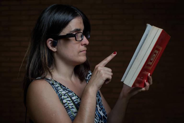 Retrato de Marina Guimarães, que adquiriu deficiência visual ainda bebê, que testa o óculos inteligente equipado com inteligência artificial lendo um livro