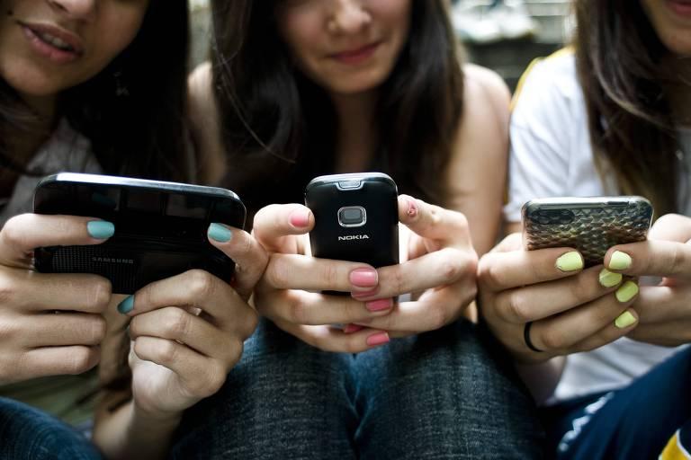 Adolescentes digitam em seus celulares