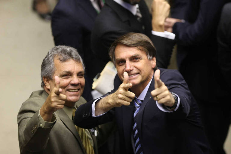 Os deputados Alberto Fraga e Jair Bolsonaro fazem sinal com as mãos imitando armas de fogo durante a votação do projeto que muda a maioridade penal