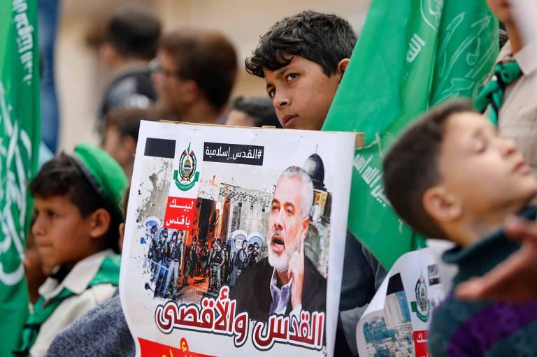 Manifestantes palestinos seguram cartaz e protestam na faixa de Gaza