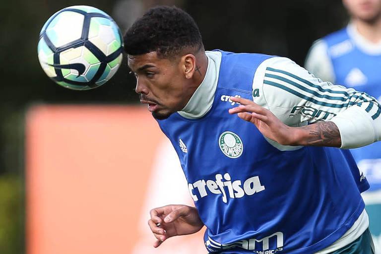 O jogador do Palmeiras Juninho cabeceia a bola com a camisa de treinamento do time