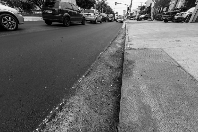 Foto mostra asfalto com carros em segundo plano