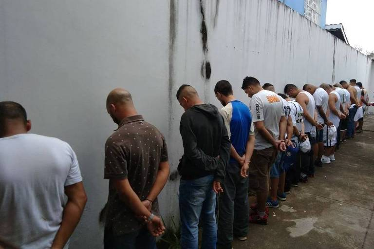 Integrantes da Torcida Jovem, do Santos, virados contra a parede, com os braços para trás.