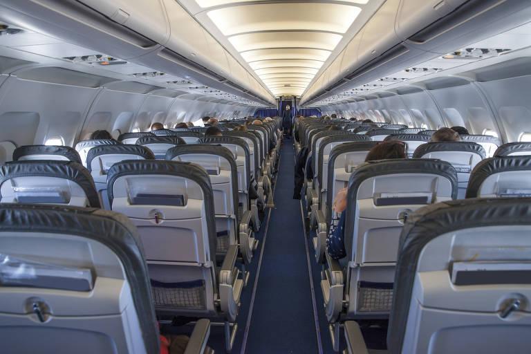 Interior de aeronave, com duas fileiras de poltronas cortadas por um corredor. Há três lugares em cada fileira