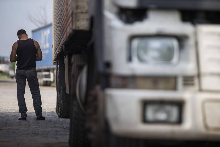 Motorista de costas ao lado de seu caminho  no estacionamento de cooperativa no Rio