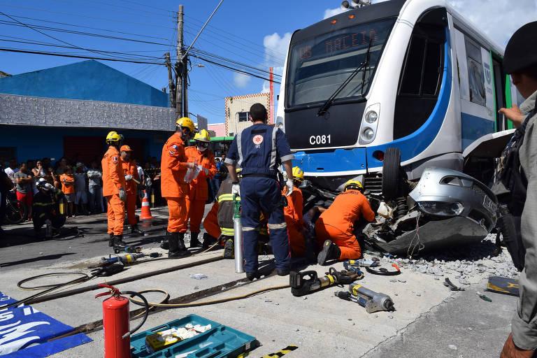 Socorristas trabalham em resgate após acidente envolvendo trem VLT e um carro