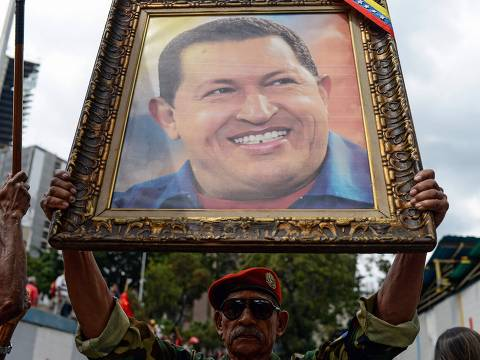 A soldier holds a portrait of late Venezuelan President Hugo Chavez during a rally to commemorate the 26th anniversary of former Chavez's 1992 military coup against the government of Carlos Andres Perez (1989-1993), at the Miraflores presidential palace, in Caracas on February 4, 2018. / AFP PHOTO / FEDERICO PARRA ORG XMIT: FPZ4588