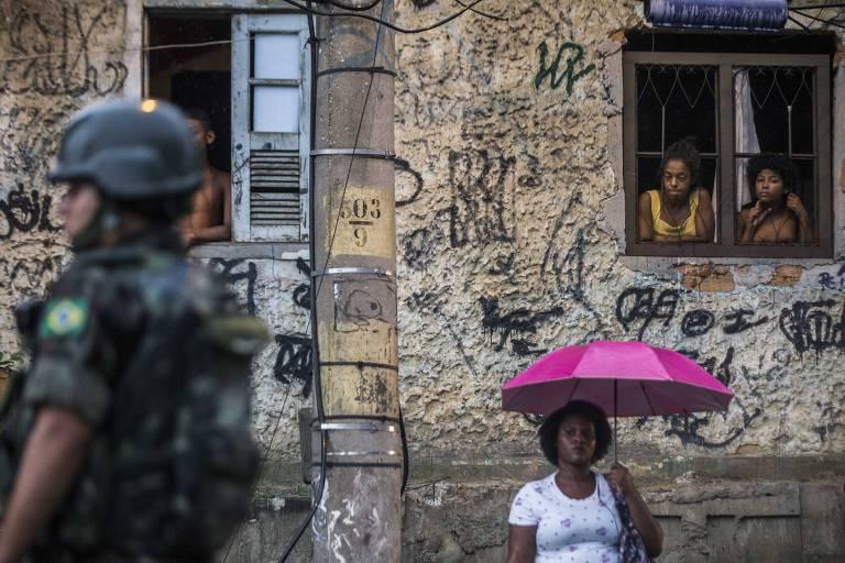 Soldado fardado diante de casa com paredes pichadas e moradores nas janelas