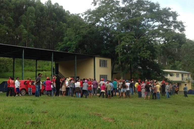 Grupo de pessoas diante de portão de uma fazenda