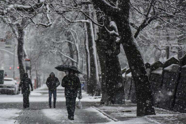 Pessoas caminham nas ruas do bairro do Brooklyn, em Nova York, durante tempestade de neve