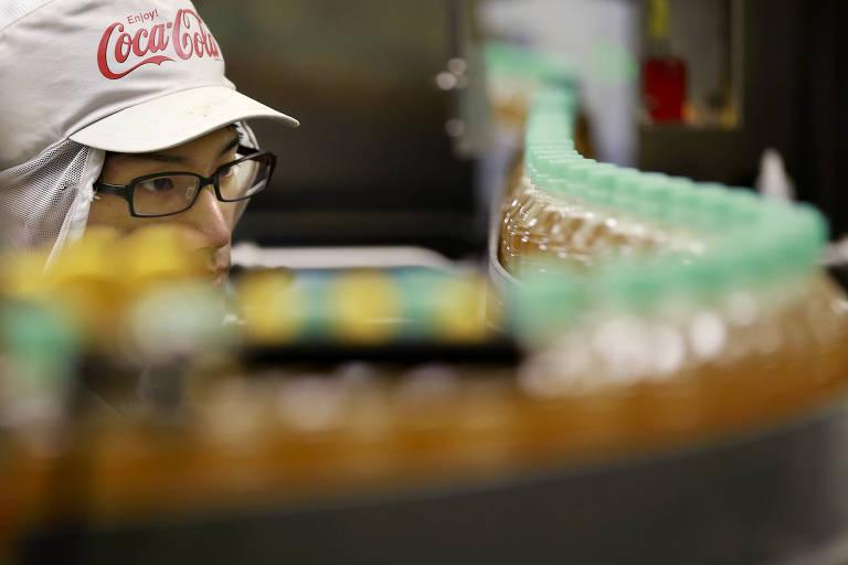 Funcionário em linha de produção da Coca-Cola em Ebina, no Japão