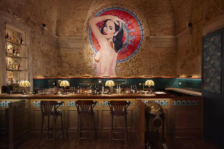 O restaurante tem um balcão em que fica o bar, com quatro cadeiras à frente. As paredes tem cor terracota e parecem rústicas. Espelhos estreitos percorrem as paredes na altura da cintura de um adulto. Há o desenho de uma mulher nua na parede do fundo