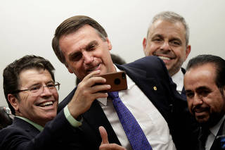 Federal deputy Jair Bolsonaro, a pre-candidate for Brazil's presidential elections, reacts during an affiliation ceremony as he joins the Liberal Social Party (PSL) in Brasilia