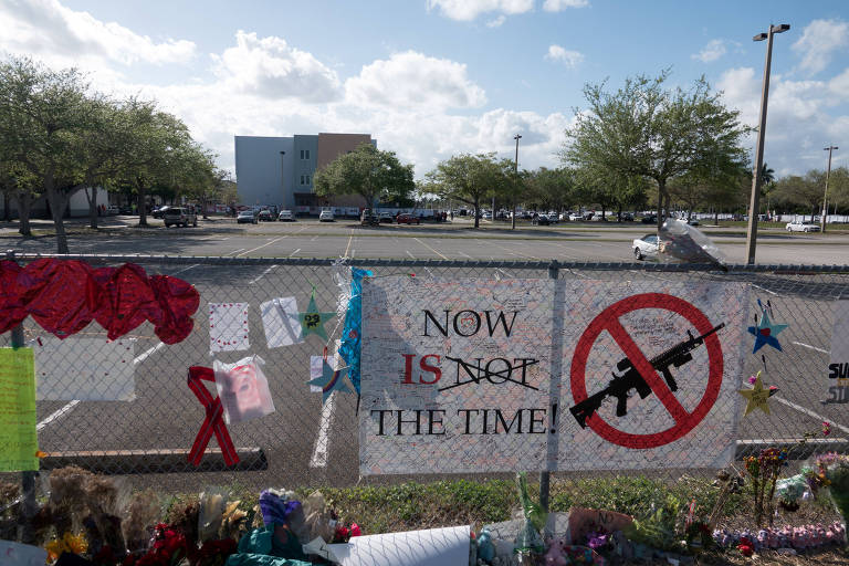 Cartaz pedindo o controle de armas de fogo é colocado ao lado de corações e faixas para as vítimas do ataque a tiros de 14 de fevereiro, na entrada da escola Marjory Stoneman Douglas, em Parkland