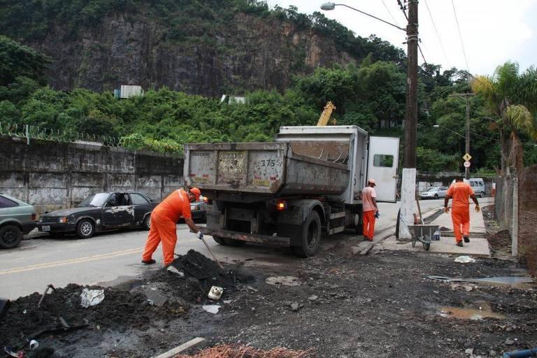 Homens com pás ao lado de caminhão fazem obras de reparo em rua após temporal em Santos