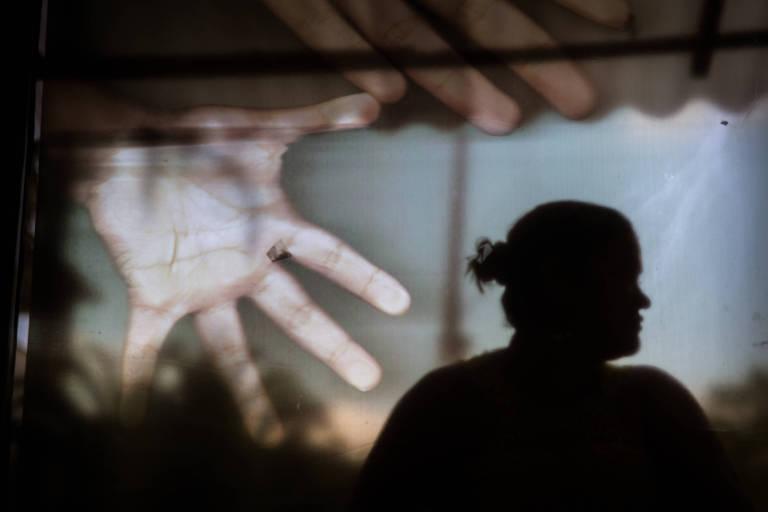 Mulher vítima de estupro fotografada em frente a janela com adesivos de mãos na ONG Cruzada do Menor