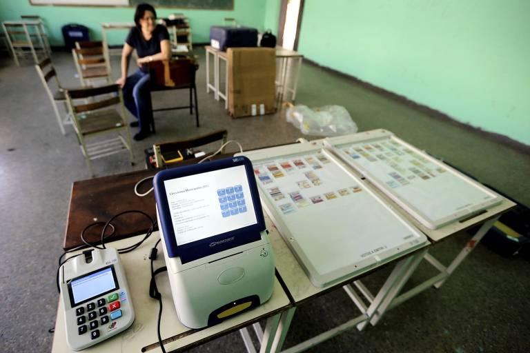 Membro do Conselho Eleitoral Nacional da Venezuela aguarda carregamento de energia de urna eletrônica