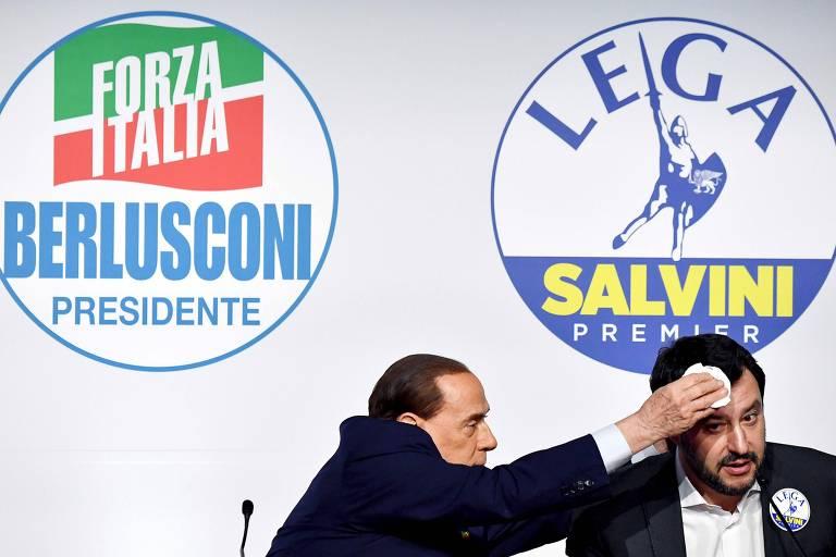 O líder da Força Itália, Silvio Berlusconi, à esq., enxuga a testa do líder na Liga, Matteo Salvini, durante entrevista coletiva em Roma