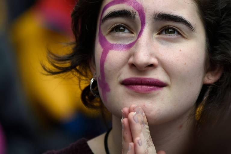 Mulher pinta o rosto com o símbolo da Vênus, durante dia de greve para defender os direitos das mulheres, em Barcelona, na Espanha