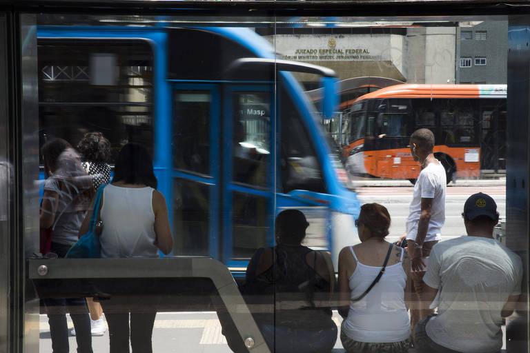 Duas pessoas aguardam de pé e três sentadas em ponto de ônibus na avenida Paulista. Elas são vistas de costas. Em frente a elas, um ônibus azul se aproxima da parada do lado esquerdo, enquanto do outro lado da avenida, um ônibus laranja passa.
