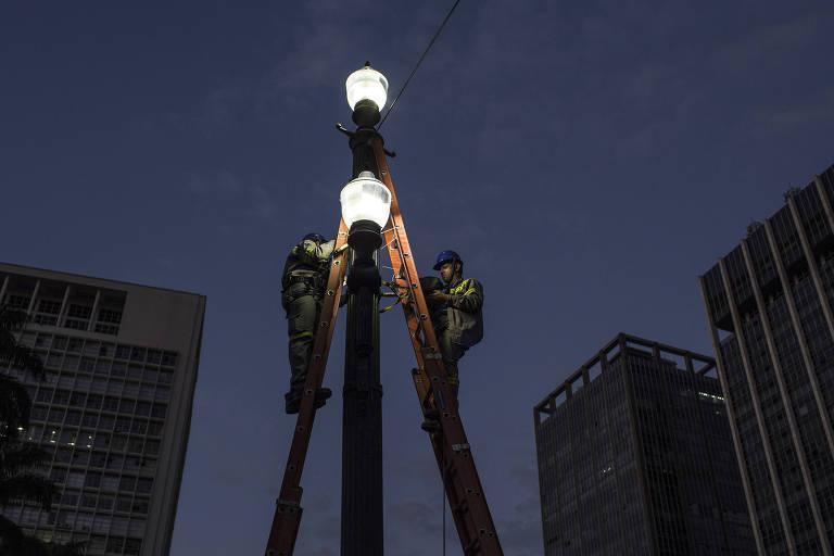 Funcionários substituem lâmpadas em poste no viaduto do Chá no centro de São Paulo