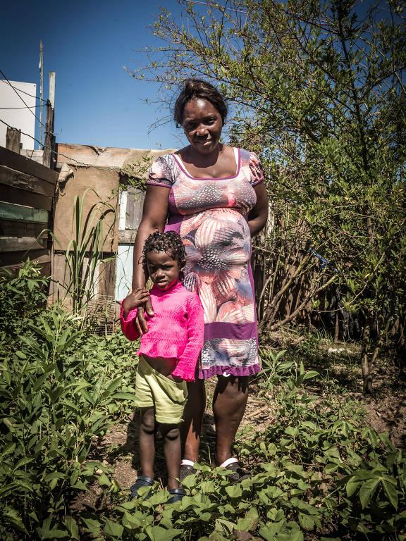 A haitiana Elisa Derisma Maesclin, 43, e a filha em casa na Ocupação Progresso, em Porto Alegre
