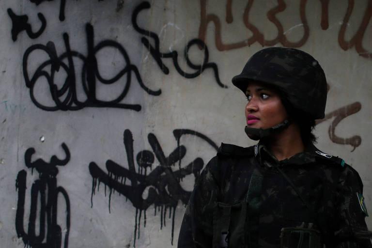 Soldado faz patrulha em rua da Vila Kennedy, na zona oeste do Rio; intervenção é criticada pelas manifestantes no centro da cidade