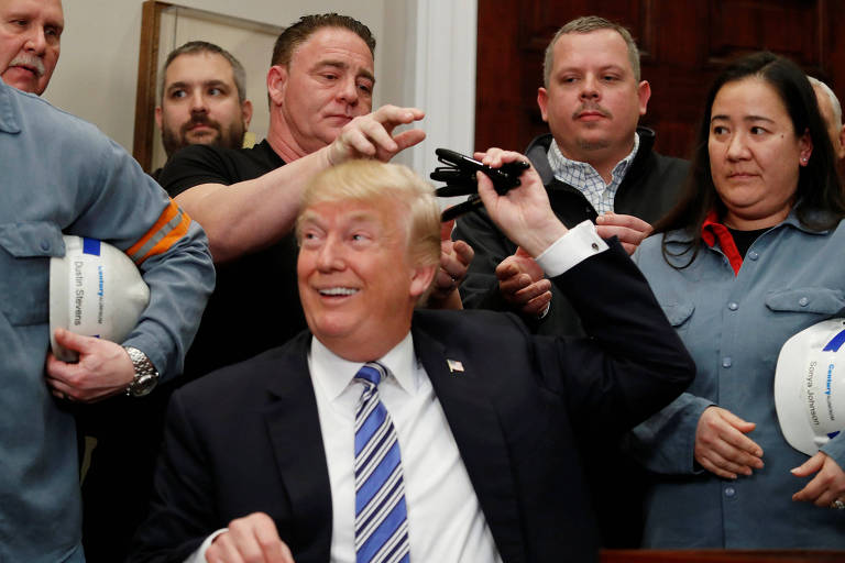 O presidente dos EUA, Donald Trump, passa para trás as canetas que usou para assinar decretos para aumentar tarifas de metais na Casa Branca
