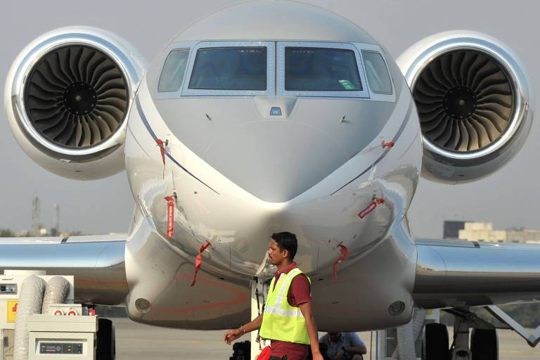 Homem passa em frente a avião durante feira do setor na Índia