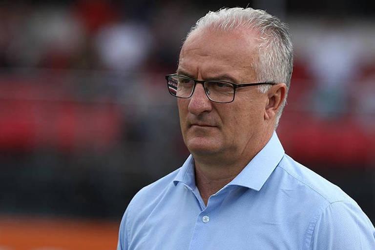 O técnico Dorival Júnior, de camisa azul e óculos, observa o time do São Paulo no Morumbi