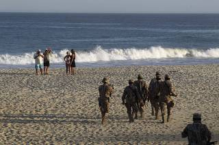 Soldiers stand guard as tourists walk along the beach in Los Cabos