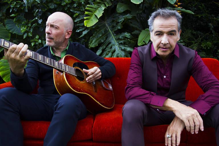 Scandurra, à esq, está sentado em um sofá vermelho segurando um violão; Nasi está sentado ao seu lado, olhando para a câmera