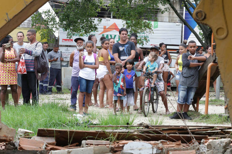 Moradores observam destroços de quiosques demolidos por retroescavadeiras durante ação da prefeitura na Vila Kennedy