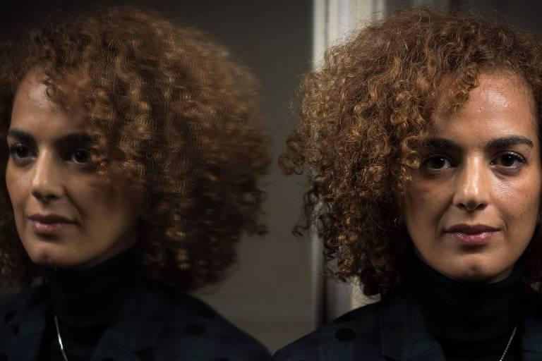 Slimani usa blusa preta até o pescoço e aparece de frente para a câmera, retratada do busto para cima. Seu rosto é refletido em um espelho ao lado.