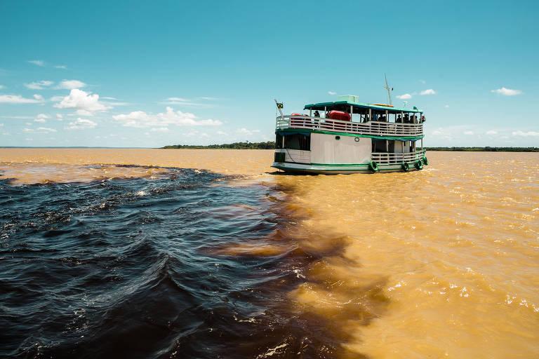 Embarcação é vista no encontro das águas do rio Negro e do rio Solimões, em Manaus