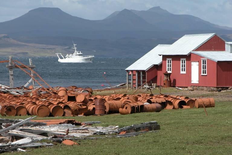 Montes de barris jogados ao lado de uma casa vermelha no arquipélago. Ao fundo, um barco navega no mar. Mais ao fundo ainda, há montanhas.