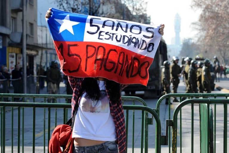 """Estudante carrega bandeira chilena com a mensagem """"Cinco anos estudando, 15 pagando"""" em protesto pela educação universitária gratuita em Santiago, em 2011"""