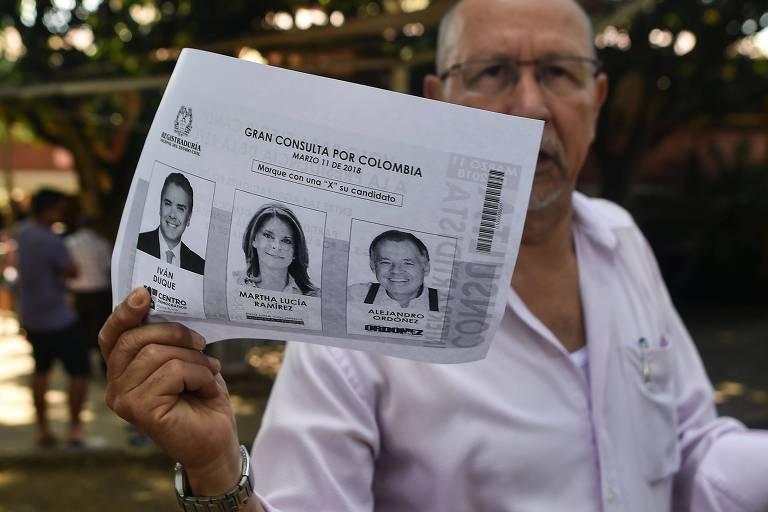 Eleitor mostra fotocópia da cédula das primárias presidenciais dos partidos de direita antes de votar em Cali, na Colômbia