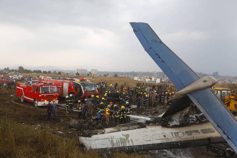 Bombeiros jogam água sobre destroços de um avião de carreira que caiu próximo ao aeroporto de Katmandu, no Nepal