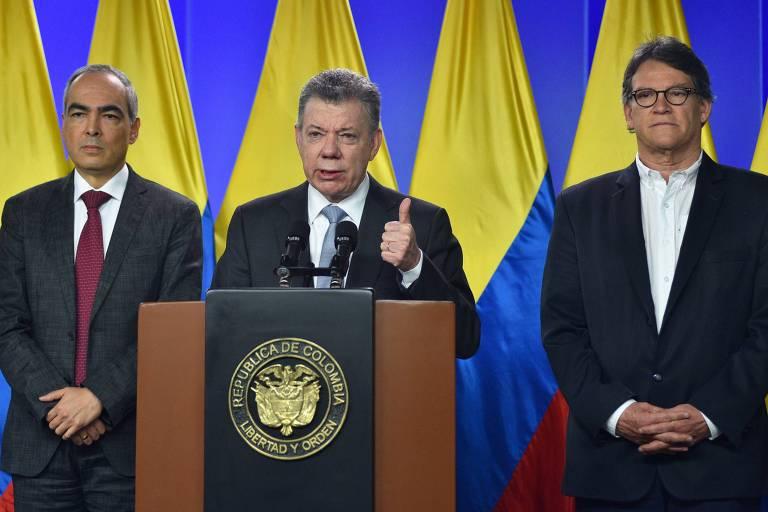 O presidente colombiano Juan Manuel Santos (centro) com o comissário de paz Rodrigo Rivera (esq.) e o negociador Gustavo Bell