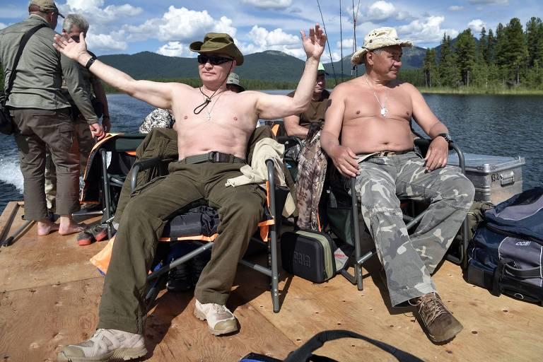 O presidente russo, Vladimir Putin, e o ministro da Defesa Serguei Shoigu, descansam depois de pescar na região de Tuva, perto da Mongólia, em 2017