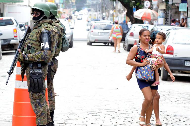 Mãe com criança de colo passa ao lado de dois soldados do Exército em bairro de São Gonçalo (RJ)