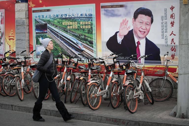 Mulher passa por pôster de propaganda com o presidente chinês Xi Jinping, em Pequim