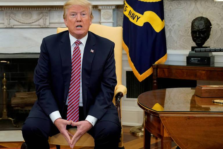 O presidente Donald Trump forma um triângulo com as mãos enquanto conversa com os jornalistas sentado no Salão Oval da Casa Branca