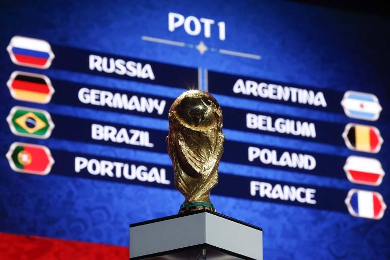 Troféu da Copa do Mundo em frente ao telão que indica as seleções presentes no pote 1 do sorteio dos grupos