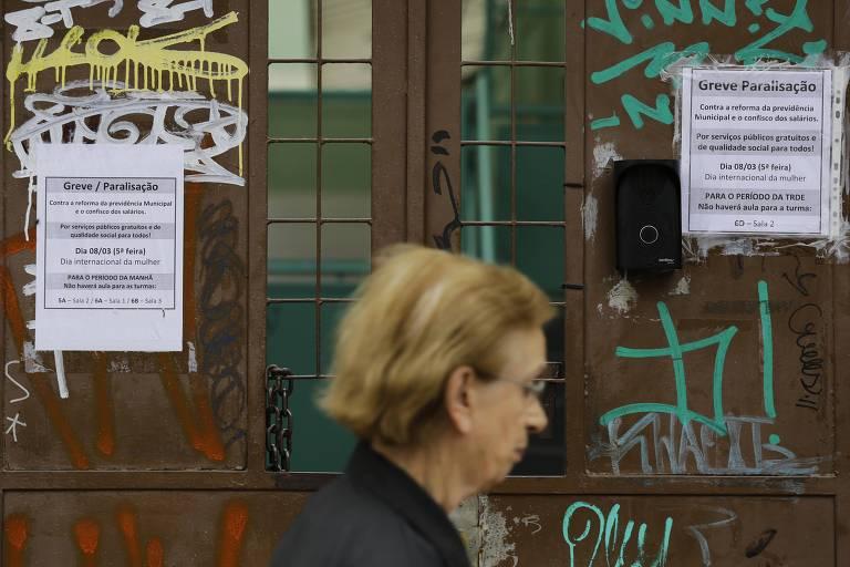 Portão da escola exibe recados da greve enquanto mulher caminha na rua