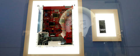 A display in the booth of Qualcomm shows the journey early 5G phone chipsets have made out of the lab, starting as a suitcase full of outsized prototype components (L), which has now been shrunk into a smartphone the size of a very thick chocolate bar (R), at Mobile World Congress in Barcelona February 27, 2018. Pictures taken February 27, 2018.   REUTERS/Yves Herman ORG XMIT: HFSYH311